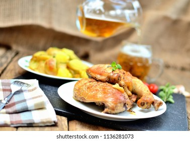 Golden grilled chicken legs on a plate, roasted potatoes and pouring cold beer into a glass, rosemary, tomatoes, oregano, salt, pepper and garlic on a wooden table - limited DOF