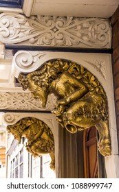 Golden grotesque stone golden satyr (faun), architectural detail of the medieval building in Brasenose College at St. Marys Passage. Oxford,UK