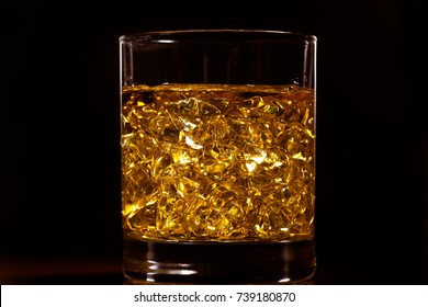 Golden hard liquor with ice on the wooden table
