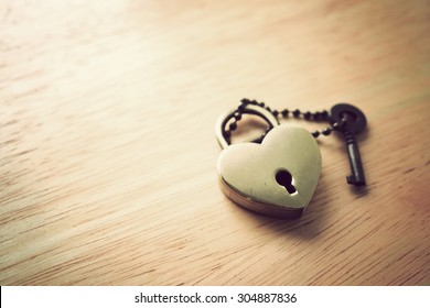 Golden heart love lock and key on wooden background. Abstract of love. Vintage effect.