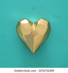 Golden heart over turquoise wooden background. Top view