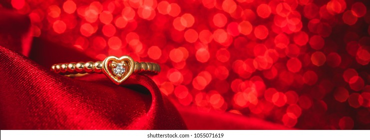 Golden heart shape ring isolated on red glitter background.