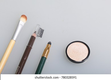 Golden highlighter in an open jar. Close to the brush for applying cosmetics and cosmetic pencils. On a white background, view from above.