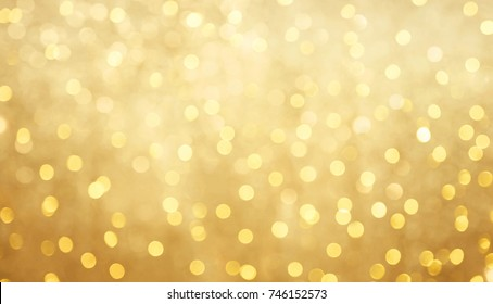 Golden Holiday bokeh background with copy space. Texture for design invite for happy New years or Christmas, Birthday, Anniversary, Wedding. Decorative Wallpaper with Golden Glitter light confetti.