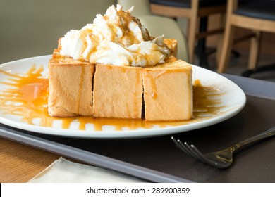 Golden honey toast in the white dish with whipped cream on top