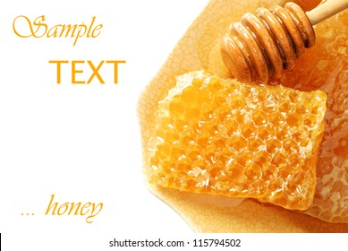 Golden honeycombs with honey and drizzler on plate with white background and copy space.