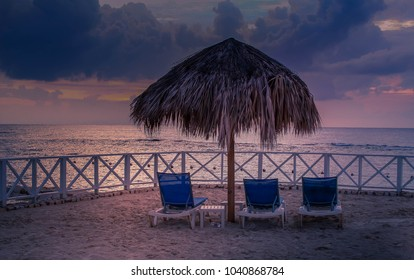 The golden hour before sunset at the beach. chairs and a beach umbrella overlooking the Caribbean Sea. Taken in Lucea, Jamaica