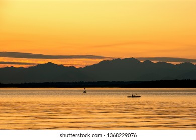 Golden hour kayak paddle with silhouetted mountains at sunset.