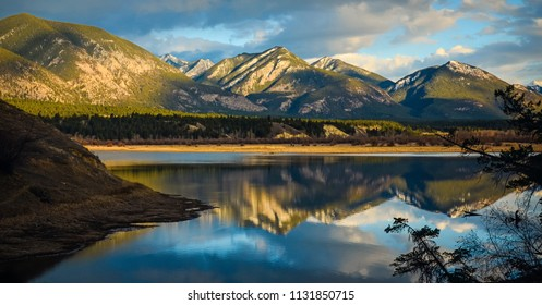 Golden hour landscape reflection of the Rocky Mountains in the Columbia Wetlands near Invermere, British Columbia, Canada
