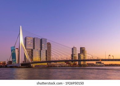 Golden hour on the city skyline of Rotterdam, the bridge in front of highrise skyscrapers. Warm colors in a gradient from orange to blue in the sky. Lights are on, the bridge is lit. The sky is clear.