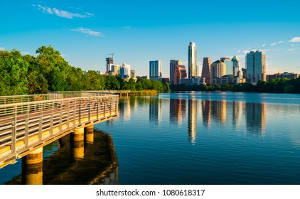 Golden hour sunrise along Town Lake Austin Texas perfect mirrored reflection Cityscape Skyline View April 2018 capital city downtown Riverside pedestrian bridge at Dawn sunrise