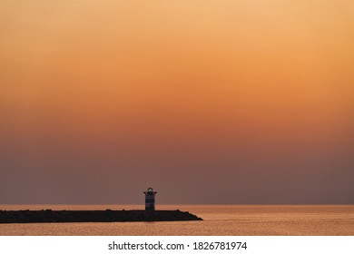 Golden hour sunset on the Scheveningen lighthouse with an even gradient orange color with space for message or text