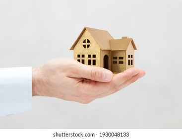 Golden house miniature in hand on gray background