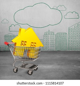 Golden house in shopping cart, with doodles of clouds and city buildings on concrete wall background, on-line shopping concepts.