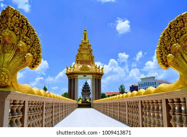 Golden Independence monument, Naga bridge walk way through the monument with beautiful clouds and blue sky background, Ta Keo, Cambodia