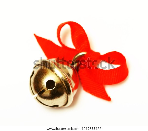 Golden jingle bell with red ribbon isolated on white background