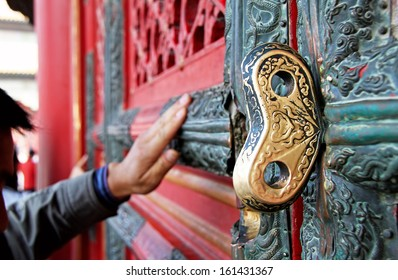 Golden key in the door of a Chinese temple. The believer touches the sacred door of Chinese temple according to ancient tradition. Canon 5D.