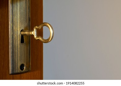 Golden key in the keyhole, macro shot, light background. Retro style. Concept and idea for history, business, security background. Write your text here.