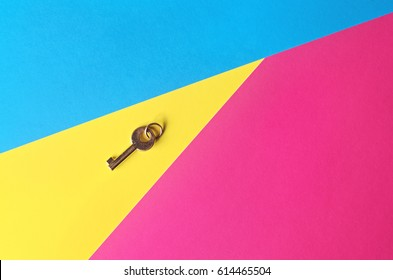 Golden key on a multicolored background, top view. Trendy colorful photo. Minimal style with colorful paper backdrop. Flat lay concept: golden key on pastel background. Trendy minimal flat lay concept