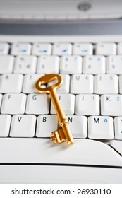 A golden key placed on the keyboard of a laptop. Very shallow depth of field, focus mainly on the tip of the key.