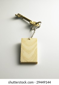 golden key with wooden key chain on the plain background