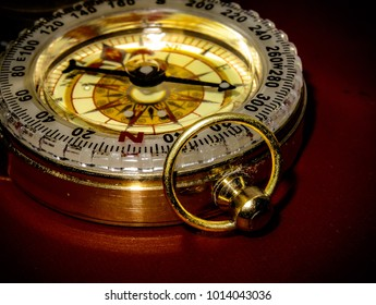A golden keychain compass on a red surface