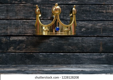 Golden king crown on wooden wall background with copy space for unique object below it. Premium product presentation concept.