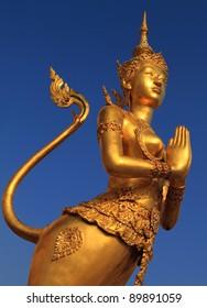 A Golden Kinnari statue att he Temple of the Emerald Buddha (Wat Phra Kaew) , Bangkok, Thailand