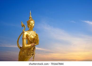 Golden Kinnari statue with beautiful sky background, Thai sculpture at Wat Phra Kaew
