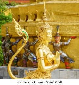 A Golden Kinnari statue in sawasdee action at the Temple of the Emerald Buddha (Wat Phra Kaew) , Bangkok, Thailand