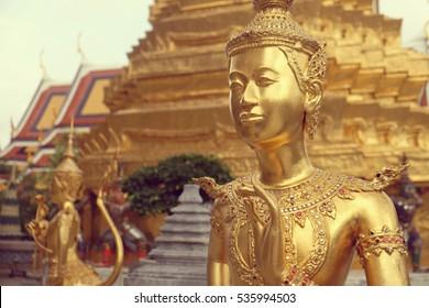 Golden Kinnari statue at Temple of Emerald Buddha (Wat Phra Kaew) in Grand Royal Palace. Half-bird, half-woman, Bangkok, Thailand
