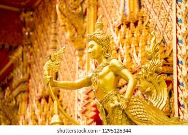 Golden Kinnari statue at temple, lamp Made from beautiful Thai art.