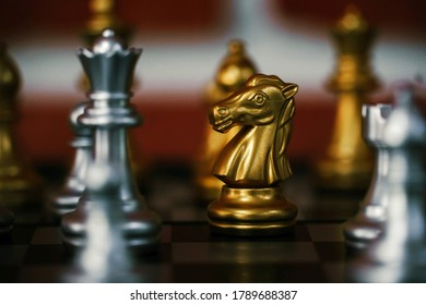 The golden knight on the board game of Chess.The knight is a piece in the game of chess and is represented by a horse's head and neck. Chess, Strategy, Game Concept. Selective focus