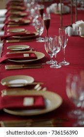 Golden knives and forks lie by golden plates on dinner table covered with red cloth