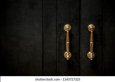 golden knob on a black wooden door