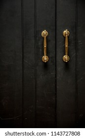golden knob on a black wooden door