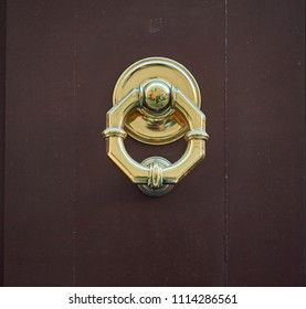 golden knocker on dark wood door