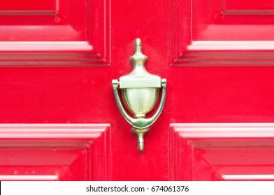 Golden knocker on old wooden red vintage door with dust.