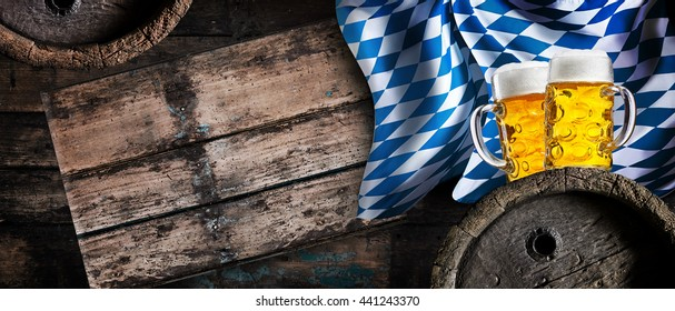 Golden lager, beer barrels and the Bavarian flag in a still life horizontal banner to celebrate the Oktoberfest in Munich in autumn, with copy space on rustic wood