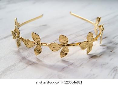 Golden laurel leaf Greek or Roman crown on marble table