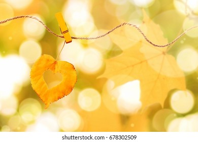 Golden leaf heart shape pinned on rope outdoors, autumn yellow bokeh. Fairy warm fall background , soft focus