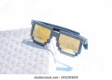 Golden lenses pixel 8bit sunglasses design shoot in a summer day closeup.Thug life model. Selective focus