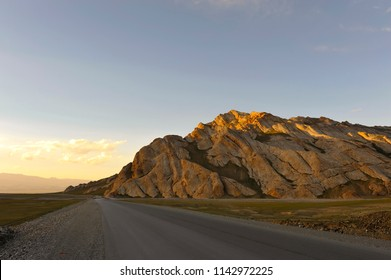 golden light clouds in the background, rock illuminated by the setting sun, a mountain highway at dusk, Kyrgyzstan