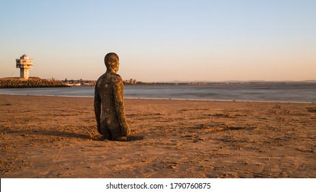 Golden light falls on the beach and an Iron Man statue before sunset on the beach at Crosby near Liverpool (England) in July 2020.