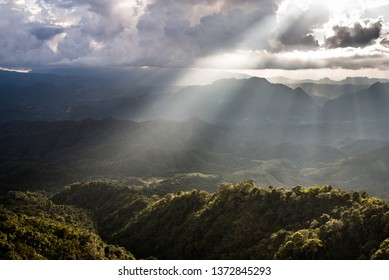 Golden light rays from clouds shining down to mountains. Sun rays over valley. Sun rays over hill. Beam of light from clouds on the mountains. Heaven in nature. Mon Pui Mok, Mae Moei, Tak, Thailand.