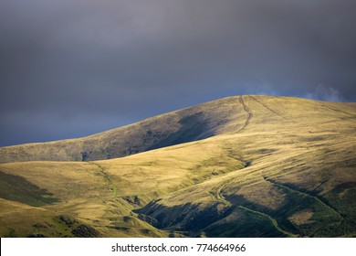 Golden light shining on hill near Sedbergh with dark clouds in background