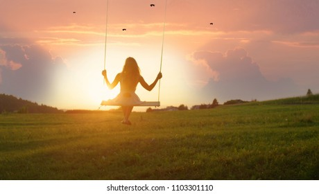 GOLDEN LIGHT SILHOUETTE: Unrecognizable girl in white dress swaying on a tree swing on peaceful evening. Lady sitting on a wooden swing and looking at golden sunset. Young woman swinging at sunrise