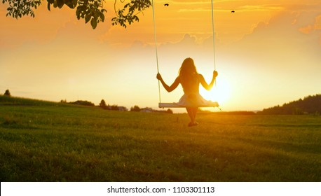 GOLDEN LIGHT SILHOUETTE: Unrecognizable girl in white dress swaying on a tree swing on peaceful evening. Lady sitting on a wooden swing and looking at golden sunset. Young woman swinging at sunrise - Shutterstock ID 1103301113