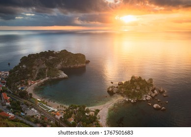 The golden light of the sunrise makes Isola Bella shine. This island is located in Sicily, Italy.