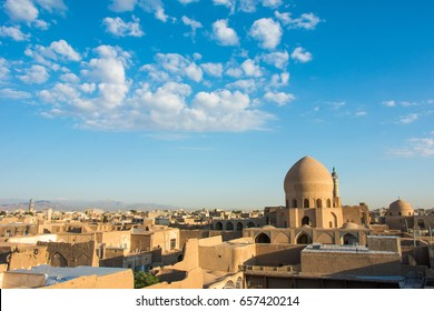 Golden light at sunrise over the Silk Road city skyline of Kashan, Iran, with a view of the domed top of the Agha Bozorg mosque and white clouds in a blue sky